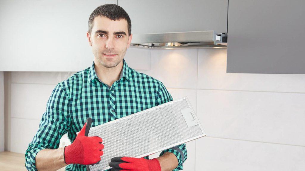 A man holding range hood filter